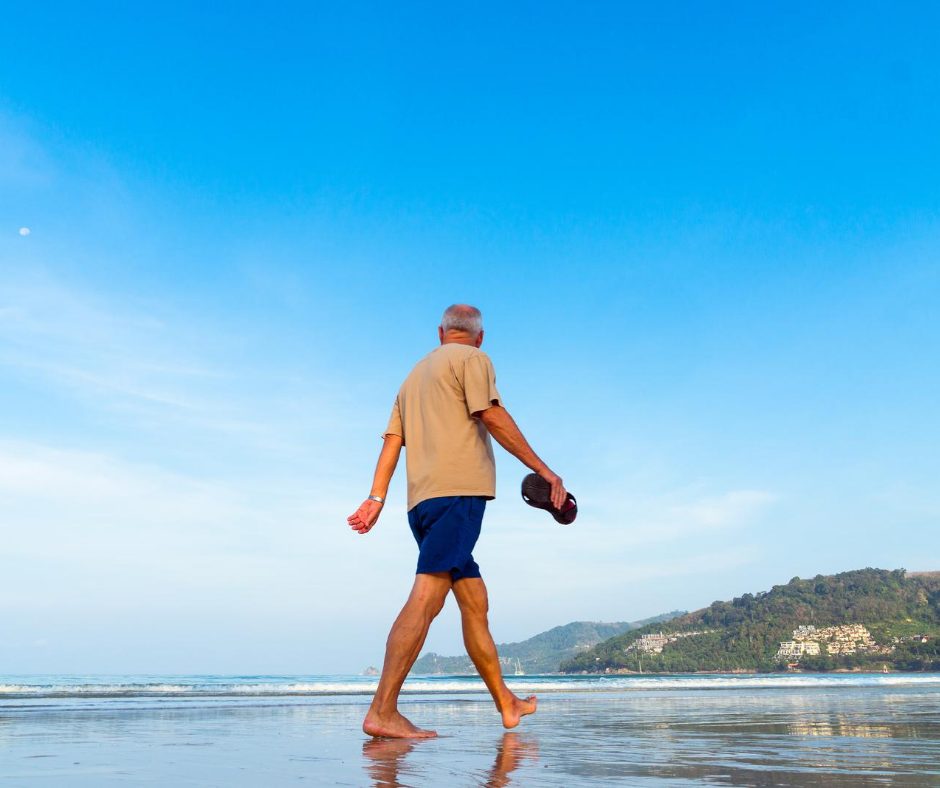 Elderly man walking on beach