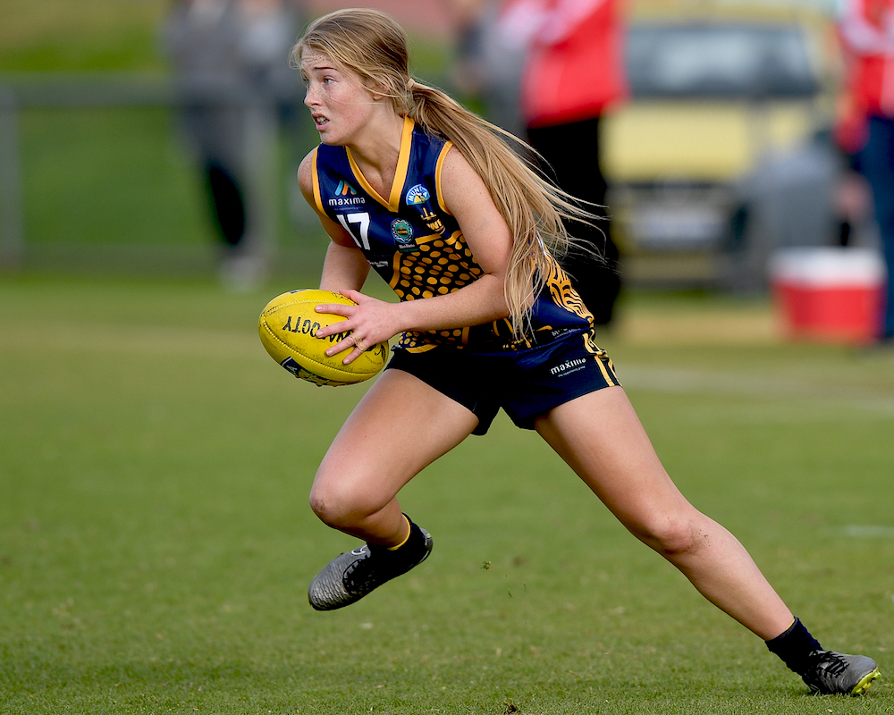 Girl running and playing AFL