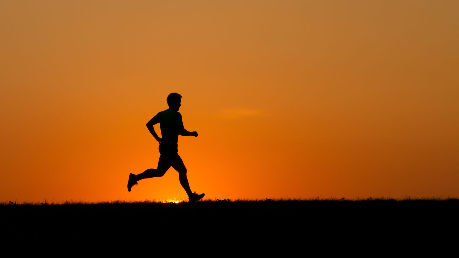 Silhouetted man jogging